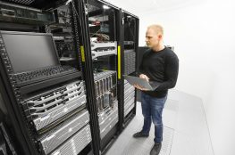 It professional or technicial consultant monitors blade servers in data rack. Shot in datacenter.